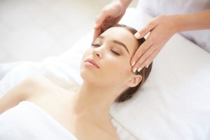 Portrait of beautiful young woman enjoying face massage in SPA while lying with eyes closed, copy space